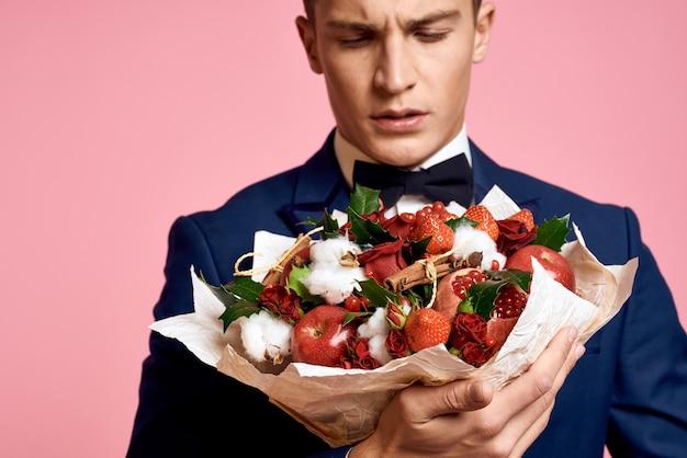 Model mężczyzna pozuje w klasycznym garniturze na tle z bukietem kwiatów