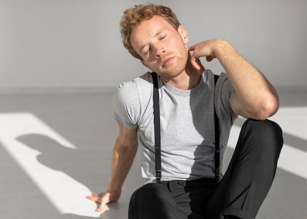 Model mężczyzna siedzi na podłodze w studio