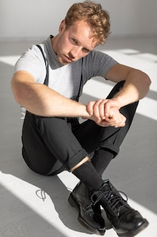 Model mężczyzna siedzi na podłodze