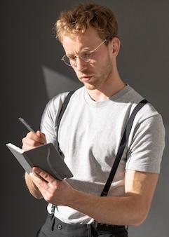 Model mężczyzna ubrany w szelki akcesoria i pisze