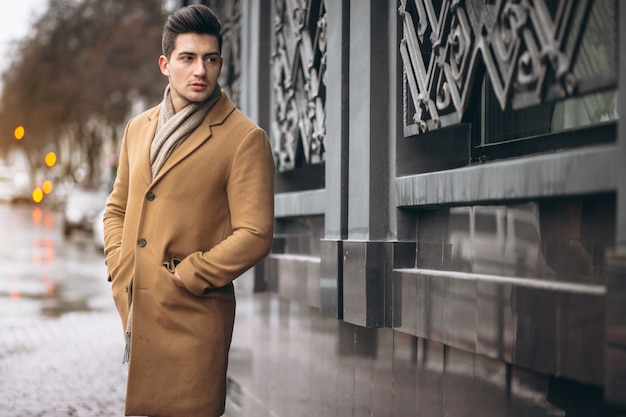 Model mężczyzna w płaszczu na zewnątrz