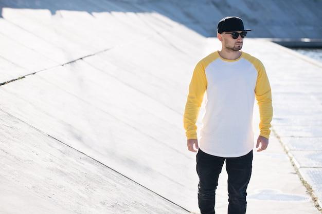 Model mężczyzna z brodą ubrany w biało-żółtą pustą koszulę z długim rękawem do makiety i czapkę z daszkiem z miejscem na twoje logo lub projekt w swobodnym miejskim stylu