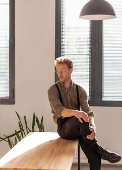 Model mężczyzna z kręconymi włosami, siedząc na stole