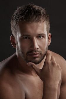 Model mężczyzna z otwartą klatką na ciemnym tle, muskularne ciało młodego mężczyzny w dżinsach. nakręcony w studio.