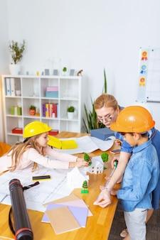 Model miasta. widok z góry nauczyciela w okularach i ciężko pracujących uczniów tworzących model inteligentnego miasta