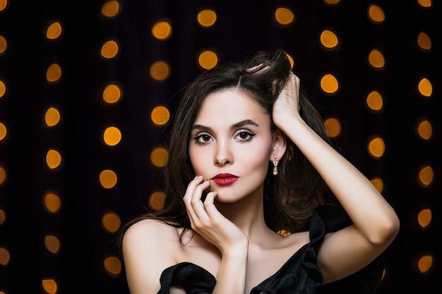 Model młoda brunetka kobieta piękny i luksusowy portret na tle złotych świateł