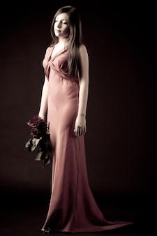 Model młoda brunetka kobieta w czerwonej długiej sukni wieczorowej stojąc i trzymając bukiet czerwonych róż
