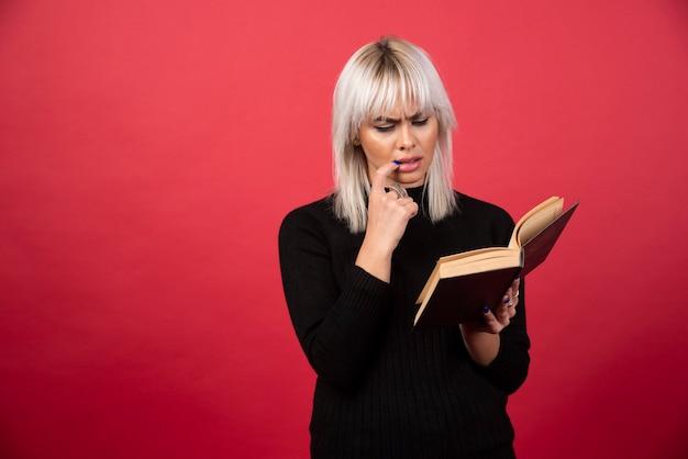 Model młoda kobieta czyta książkę na czerwonej ścianie.
