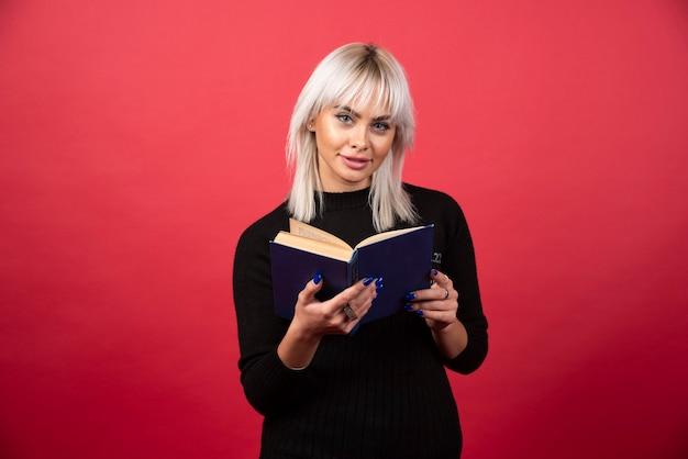 Model młoda kobieta czyta książkę na czerwonym tle. wysokiej jakości zdjęcie