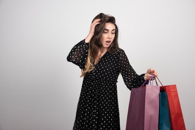 Model młoda kobieta niosąca wiele toreb na zakupy