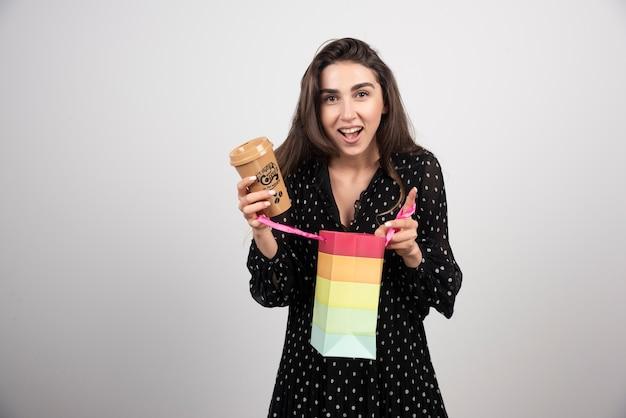 Model młoda kobieta, otwierając torbę sklepową i trzymając filiżankę kawy