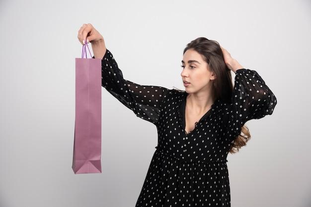 Model młoda kobieta patrząc na pustą torbę na zakupy