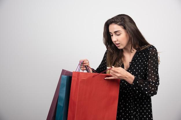 Model młoda kobieta patrząc na torby na zakupy