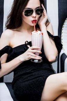 Model młoda kobieta piękna i luksusowa siedzi przy koktajlu truskawkowym w czarno-białe paski krzesło modne i stylowe w okularach przeciwsłonecznych
