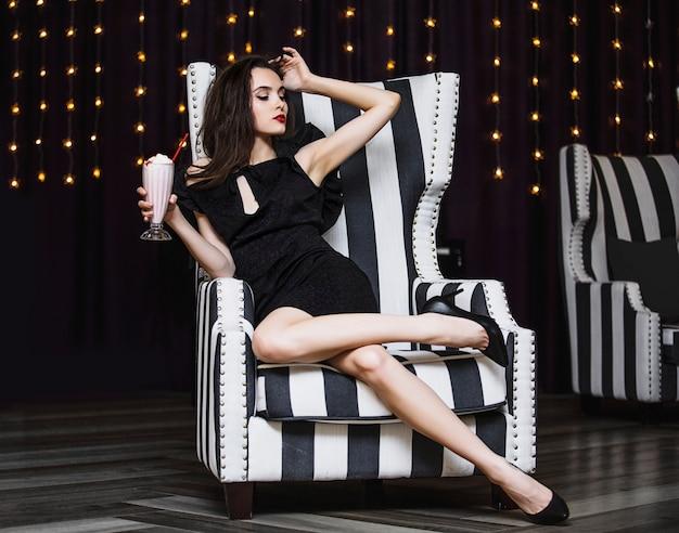 Model młoda kobieta piękna i luksusowa siedzi przy koktajlu truskawkowym w czarno-białe paski krzesło modne i stylowe