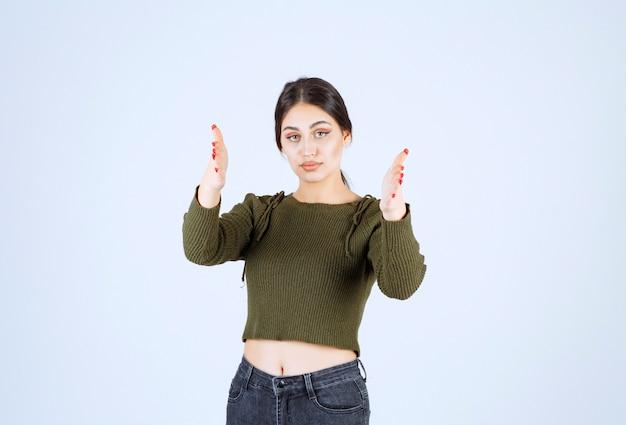 Model młoda kobieta poważne pokazano w aparacie rękami nad białą ścianą.