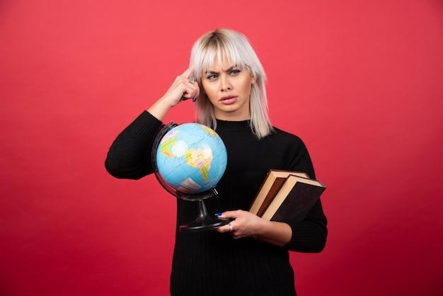Model młoda kobieta pozuje z książkami i kulą ziemską na czerwonej ścianie.