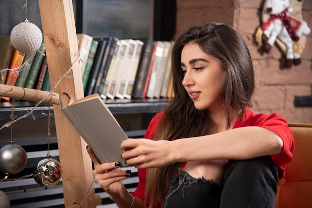 Model młoda kobieta siedzi i czyta książkę.