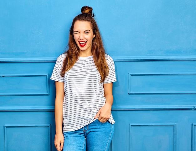 Model młoda kobieta stylowa w letnie ubrania z czerwonymi ustami, pozowanie w pobliżu niebieską ścianą. mrugnięcie