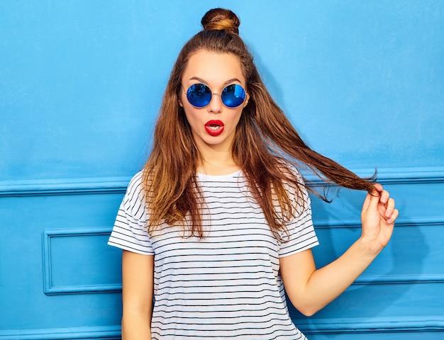 Model młoda kobieta stylowa w letnie ubrania z czerwonymi ustami, pozowanie w pobliżu niebieską ścianą. zabawa z jej włosami