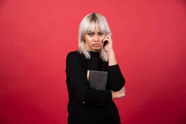 Model młoda kobieta trzyma książkę na czerwonej ścianie.
