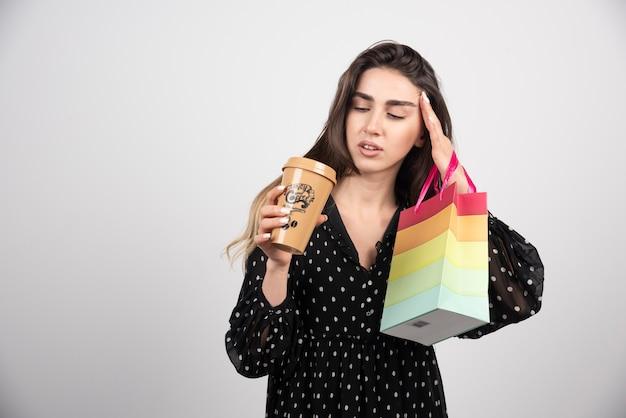 Model młoda kobieta trzyma torbę sklepową przy filiżance kawy