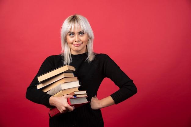 Model młoda kobieta trzyma wiele książek na czerwonej ścianie.