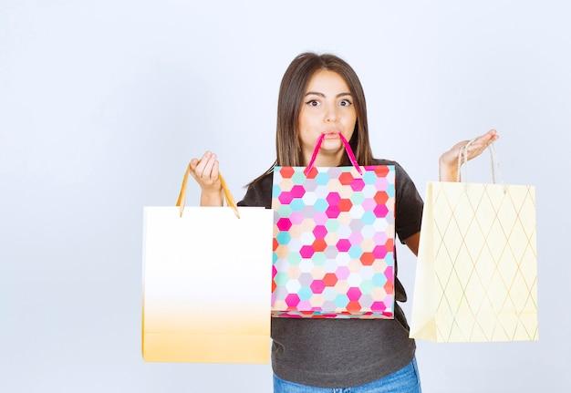 Model młoda kobieta trzyma wiele toreb na zakupy na białym tle.