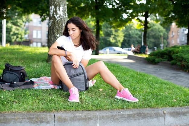 Model młoda kobieta z telefonem siedzi na trawie. rozmowy telefoniczne