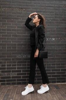 Model młoda modna kobieta w modnej marynarce w stylowej koszulce w casualowe dżinsy vintage w skórzanej torbie mody w pobliżu ceglanej czarnej ściany. zbliżenie ciała kobiety. nowa kolekcja odzieży młodzieżowej dla kobiet.