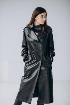 Model młodej kobiety na sobie długi czarny skórzany płaszcz