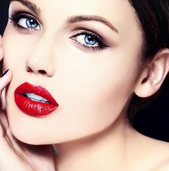 Model młodej kobiety rasy białej z jasnym makijażem, idealną czystą skórą i kolorowymi czerwonymi ustami