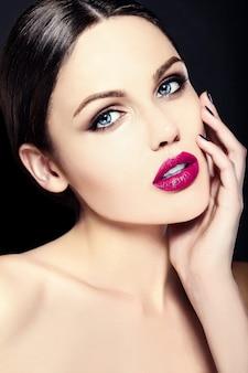 Model młodej kobiety rasy białej z jasnym makijażem, idealną czystą skórą i kolorowymi różowymi ustami
