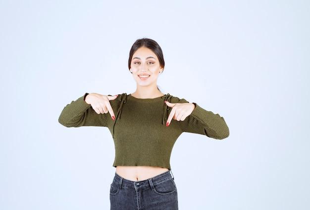 Model młodej kobiety stojącej i wskazującej palcami w dół.