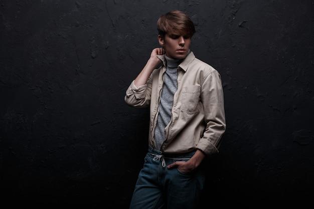 Model młody mężczyzna w modnej wiosennej lekkiej kurtce w vintage szary sweter w dżinsach z modną fryzurą pozuje w pokoju przy czarnej ścianie. stylowy, niesamowity facet. amerykański styl