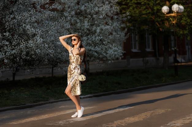 Model na spacer w lecie. letnia sukienka. kwitnące drzewa w tle