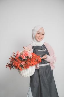 Model nosi hidżab, trzymając kwiat na beżowym tle na białym tle. stylowa muzułmańska kobieta trzyma wiadro kwiatów