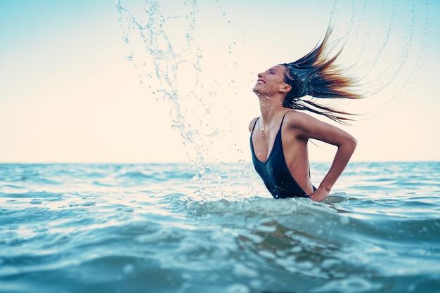 Model piękna dziewczyna przelewanie wody z włosami. młoda kobieta pływa w morzu. ciesz się życiem