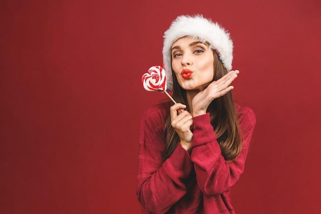 Model piękna dziewczyna w kapeluszu świętego mikołaja z czerwonymi ustami i boże narodzenie cukierki lizak, wskazując ręką
