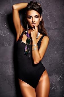 Model piękna dziewczyna w letniej czarnej bieliźnie z jasnym makijażem kreatywnych pozowanie w pobliżu szarej ściany