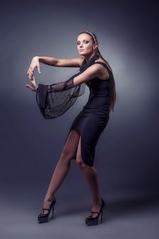 Model piękne kobiety w modne ubrania i akcesoria strzał na białym tle na czarnym tle