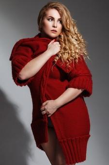 Model plus size w bieliźnie i czerwonym płaszczu z dzianiny