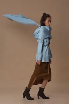 Model pozuje na całej długości z latającym ogonem w niebieskiej bawełnianej bluzce.