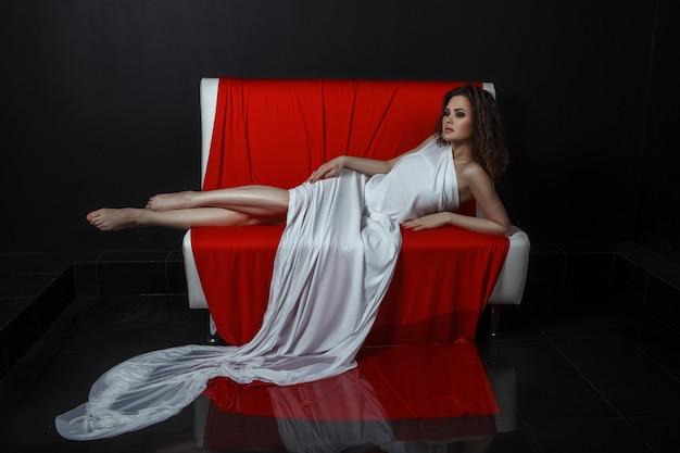 Model pozuje w ciemnym pokoju z długim czerwonym materiałem