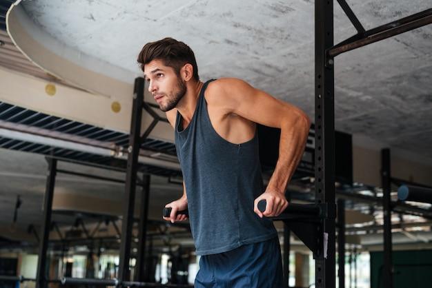 Model robi ćwiczenia na siłowni. odwracając wzrok