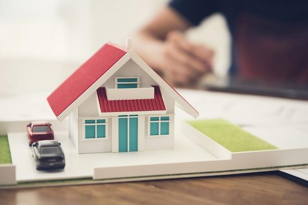 Model samochodu i domu na stole z rozmycia ludzi pracujących
