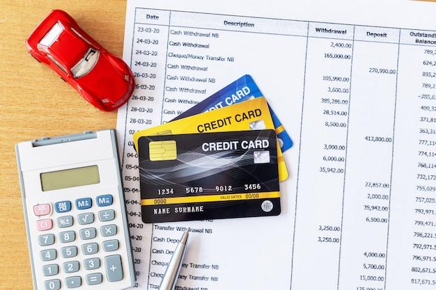 Model samochodu i kalkulator na wyciągu bankowym i karty kredytowej na drewnianym stole.