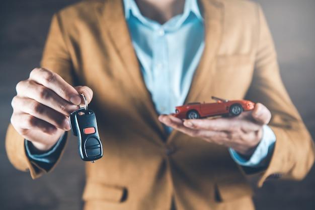 Model samochodu ręka mężczyzny z kluczem na ciemnym tle