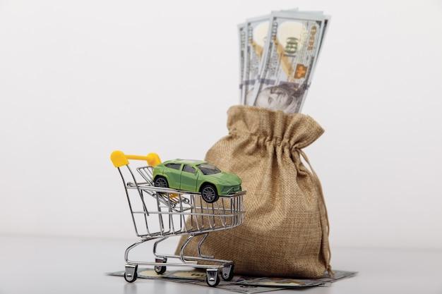 Model samochodu w koszyku z worek pieniędzy na białym tle
