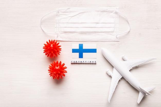 Model samolotu i maska na twarz oraz flaga finlandii. koronawirus pandemia. zakaz lotów i zamknięte granice dla turystów i podróżników z koronawirusem covid-19 z europy i azji.
